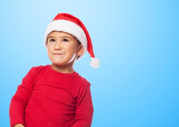 Kleiner junge weihnachten mit einem sankt-hut feiert