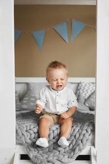Kleiner junge weint, während er auf dem bett sitzt