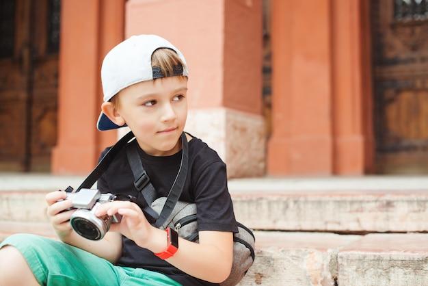 Kleiner junge will fotograf werden. junge mit einer digitalkamera, die bilder macht. schulprojekt für kinder. zukünftiger beruf.