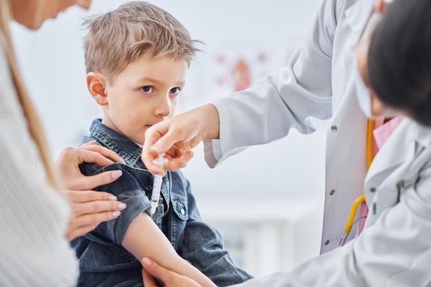 Kleiner junge wird vom kinderarzt geimpft