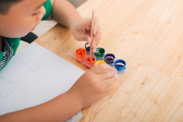 Kleiner junge zeichnet einen pinsel und malt sein erstes bild. konzentriere dich auf die zeichnung