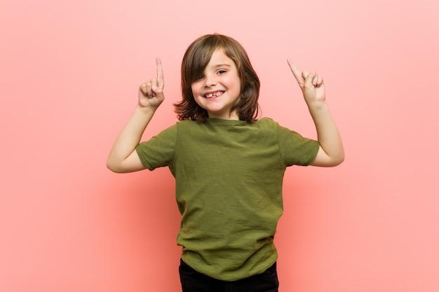 Kleiner junge zeigt mit beiden vorderfingern an, eine leerstelle oben zu zeigen.