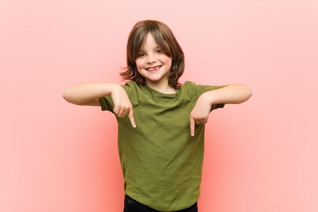 Kleiner junge zeigt mit den fingern nach unten, positives gefühl.