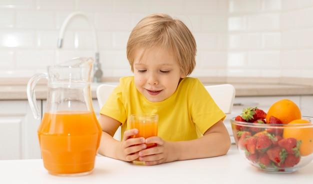 Kleiner junge zu hause, der früchte isst und saft trinkt