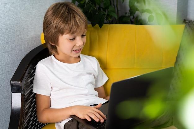 Kleiner junge zu hause mit laptop online lernen