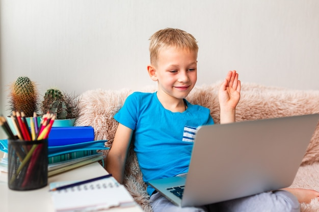 Kleiner junger schuljunge, der zu hause mit einem laptop und klassennotizen arbeitet, die in einer virtuellen klasse studieren. fernstudium und lernen, e-learning, online-lernkonzept während der quarantäne