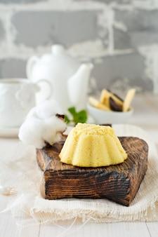 Kleiner käsekuchen mit weißer schokolade und geschlagenen proteinen auf hellem hintergrund.