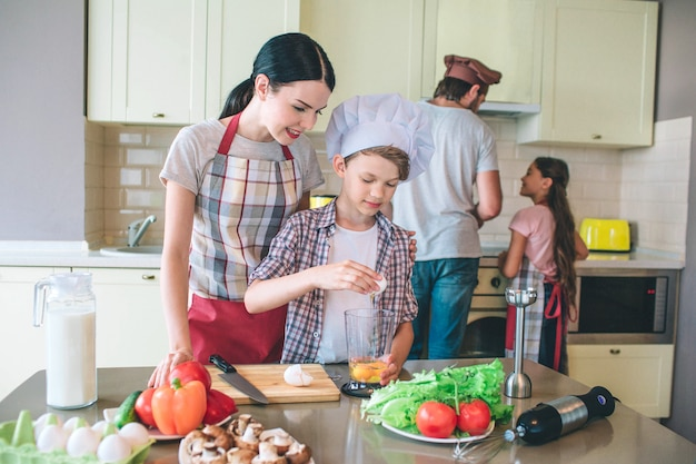 Kleiner kauf gießt ei aus seiner schale. frau schaut es an und kontrolliert. kleines mädchen hilft seinem vater, am ofen zu kochen. sie sieht ihn an.