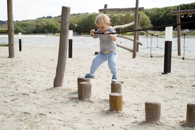 Kleiner kaukasischer blonder junge, der an einem sonnigen herbsttag auf kinderspielplatz spielt