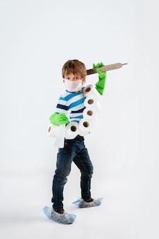 Kleiner kaukasischer junge als krieger im kampf gegen die coronavirus-pandemie, mit einem schild, einem speer und einem toilettenpapier-bandoleer, angreifend