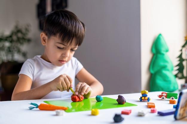 Kleiner kaukasischer junge, der mit farbigem plastilin spielt und figuren auf dem weißen tisch macht. glückliche kinderidee