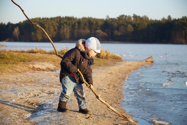 Kleiner kaukasischer junge, der nahe flussufer steht und mit holzstab spielt