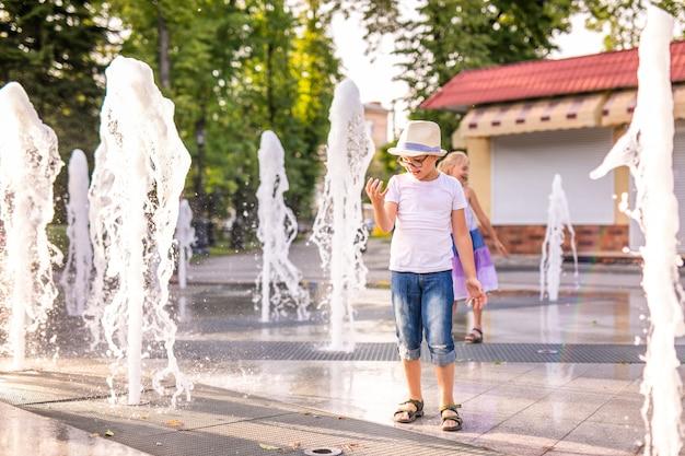Kleiner kaukasischer junge im hut, der spielt und spaß mit wasser im brunnen im sonnigen sommerpark hat