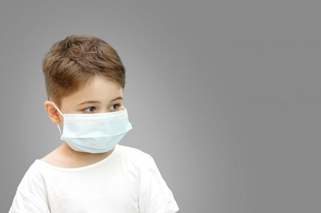 Kleiner kaukasischer junge in der medizinischen maske auf lokalisiertem hintergrund