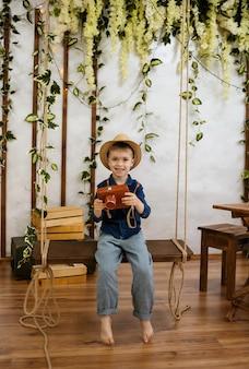 Kleiner kaukasischer junge in einem strohhut sitzt auf einer holzschaukel mit einer kamera auf der veranda