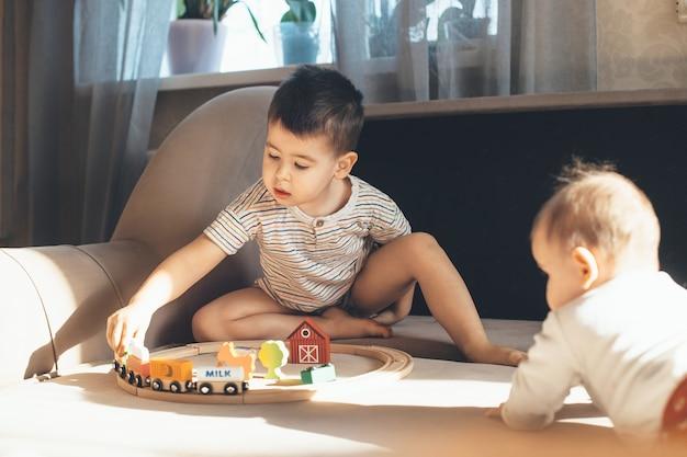 Kleiner kaukasischer junge spielt auf der couch mit einer spielzeugeisenbahn, während neugeborenes geschwister ihn beobachtet