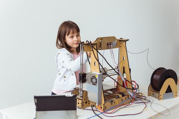 Kleiner kinderarchitekt mit 3d-drucker. schulmädchen, technologien und studienkonzept.
