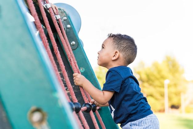 Kleiner kinderjunge, der ein seil im park klettert.