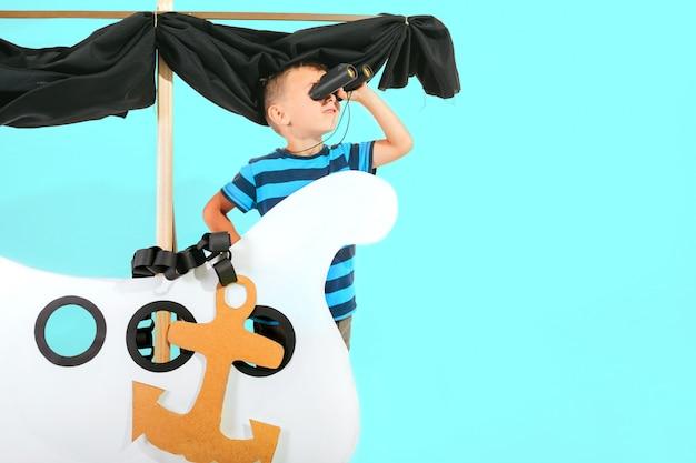 Kleiner kinderjunge, der mit pappschiff auf blauer wand spielt