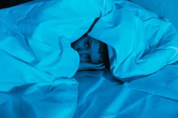 Kleiner kinderjunge liegt in dunkler nacht im bett und hat angst vor albträumen und schrecklichen träumen bei kindern