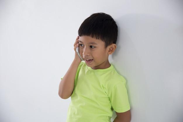 Kleiner kleiner junge, der smartphone benutzt