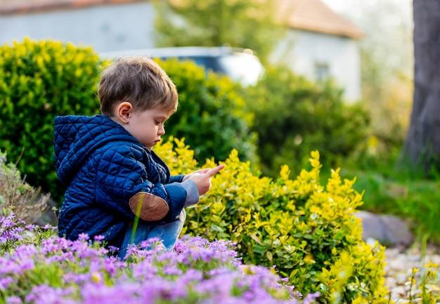 Kleiner kleinkind, der mit blumen im garten spielt