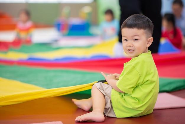Kleiner kleinkindjunge, der an der innengymnastikübung ausarbeitet