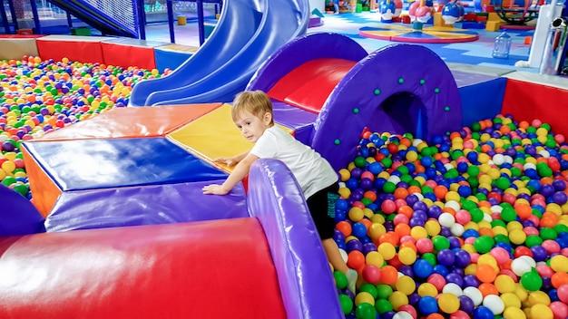 Kleiner kleinkindjunge, der auf dem spielplatz im einkaufszentrum über viele bunte plastikbälle geht und klettert