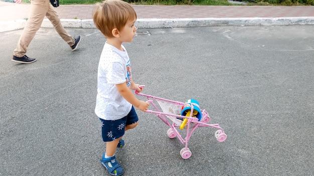 Kleiner kleinkindjunge, der auf der straße geht und spielzeugkinderwagen für puppen schiebt