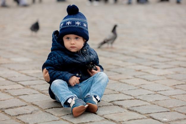 Kleiner kleinkindjunge, der auf pflastersteinen im stadtplatz sitzt