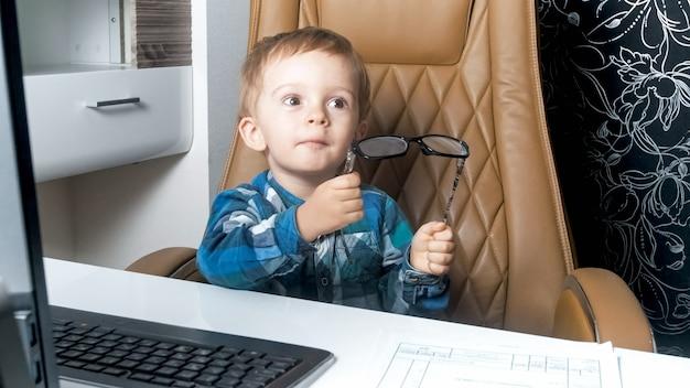 Kleiner kleinkindjunge, der eine brille im büro im sessel hält.