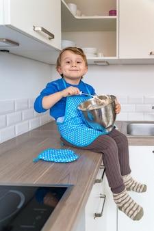 Kleiner kleinkindjunge, der küchenschürze trägt, die apfel-hauskuchen backt
