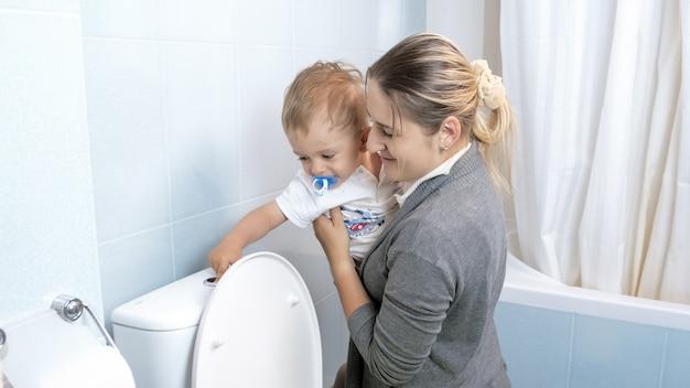 Kleiner kleinkindjunge, der mit junger mutter wasser in der toilette spült.
