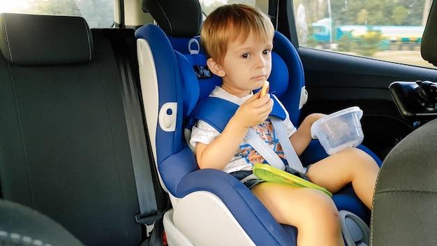 Kleiner kleinkindjunge, der sich hungrig fühlt und isst, während er mit dem auto im kindersitz fährt