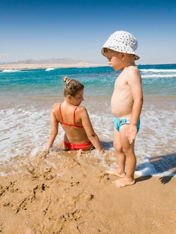 Kleiner kleinkindjunge und mutter, die sich am sandstrand in warmen meereswellen entspannen. familie, die sich während der sommerferien entspannt und gute zeit hat.