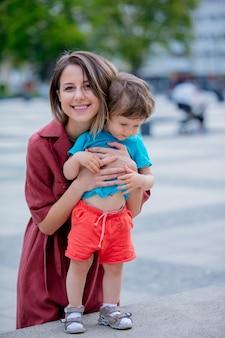 Kleiner kleinkindjunge und mutter haben spaß auf der stadtstraße