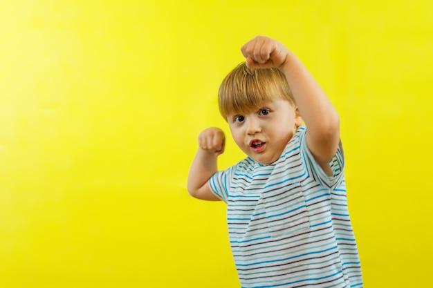 Kleiner kleinkindjunge zeigt kraft und mut, hebt die arme mit fäusten, die muskeln und kraft zeigen.