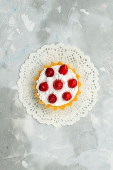 Kleiner köstlicher kuchen der oberen entfernten ansicht mit sahne und roten früchten lokalisiert auf dem leichten oberflächentee