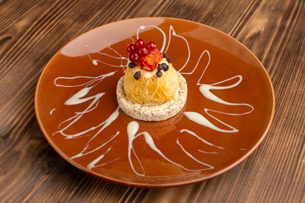 Kleiner köstlicher kuchen mit frischen preiselbeeren des crackers innerhalb der braunen platte auf holz