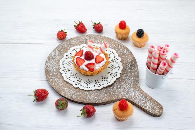 Kleiner köstlicher kuchen mit sahne und geschnittenen roten frischen erdbeerkuchen auf weißen, kuchenbeeren-süßen backfrüchten