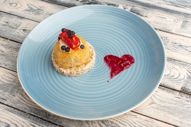 Kleiner köstlicher kuchen mit sahne und marmelade oben in der blauen platte auf grau