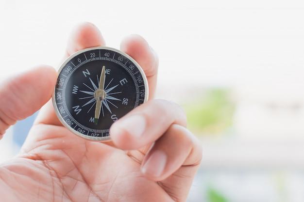 Kleiner kompass in der hand, um ein abenteuer oder eine reise zu beginnen