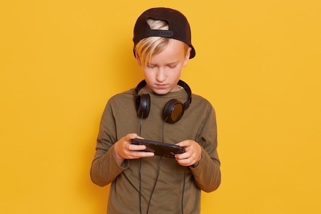 Kleiner konzentrierter kerl, der lässiges hemd und mütze trägt, online-videospiele mit handy spielt und mit kopfhörern posiert