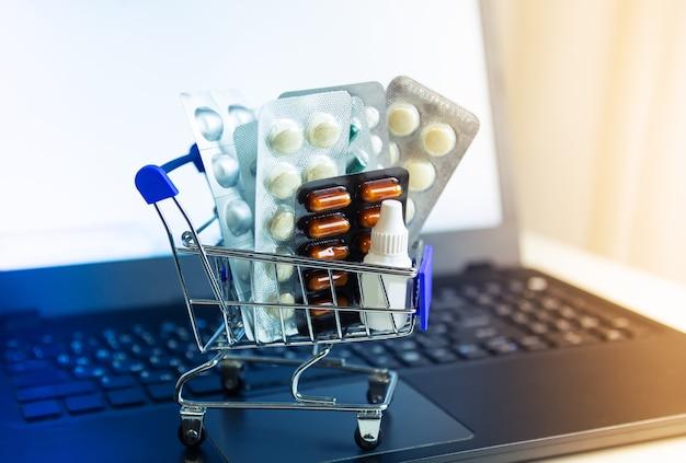 Kleiner korb mit medikamenten-nahaufnahme. laptop bildschirm. konzept für den online-kauf von medikamenten.