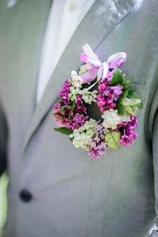 Kleiner kreis aus flieder auf der jacke des bräutigams