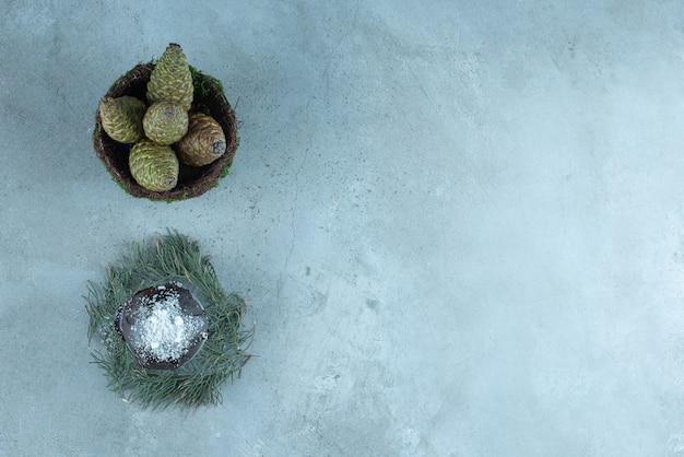 Kleiner kuchen auf einem stapel tannenblätter und eine schüssel tannenzapfen auf marmor.