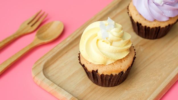 Kleiner kuchen auf einer hölzernen platte und einem rosa hintergrund.