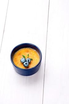 Kleiner kuchen crème brlée mit unterschiedlicher füllung auf einem weißen teller. weißer holztisch. stillleben. platz kopieren