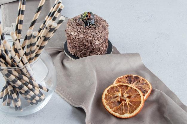 Kleiner kuchen, getrocknete zitronenscheiben und ein bündel strohpfeifen auf marmorhintergrund.