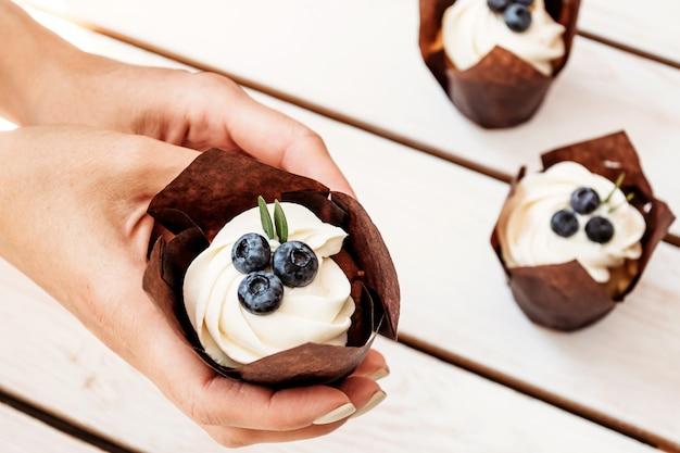 Kleiner kuchen in der weiblichen hand von patissier holiday-muffins mit sahne und beeren in der einzelnen papierverpackung